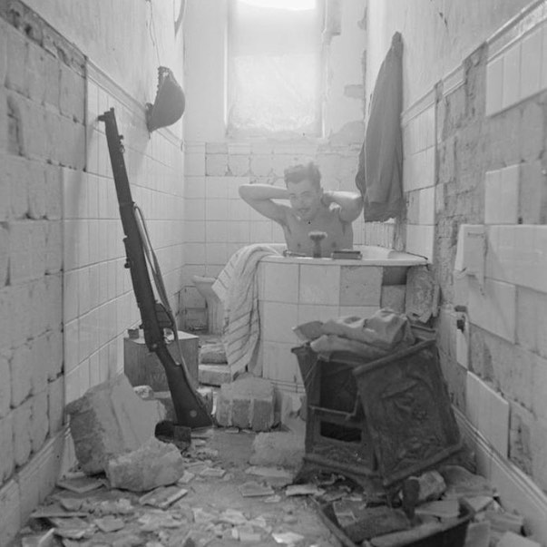 An Eight Army solider takes a bath amongst the ruins of Tobruk