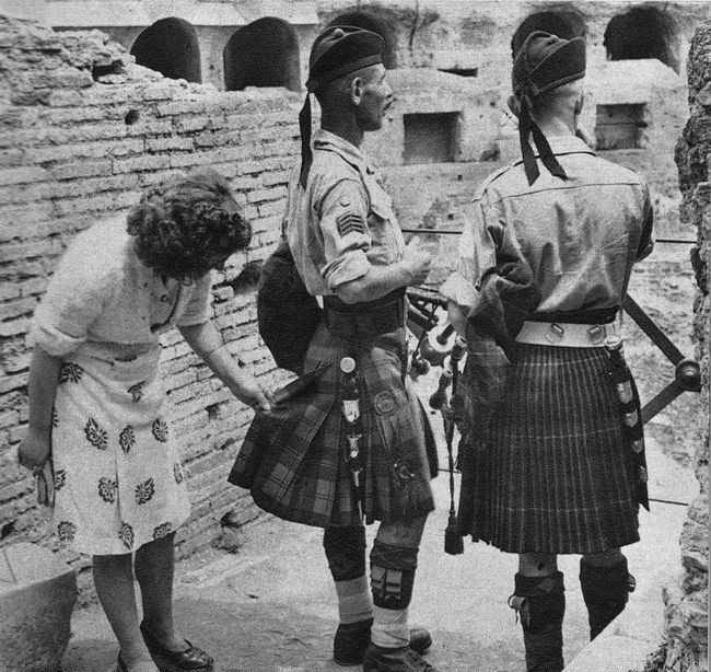 A curious Italian woman inspects the kilt of a Scottish soldier