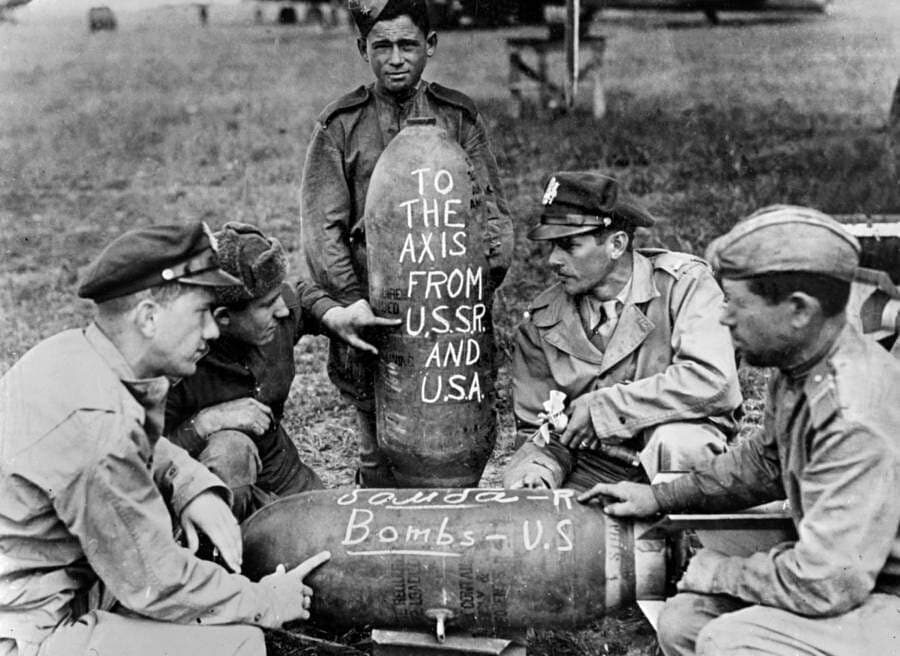 Soviet and American airmen pose with the bombs